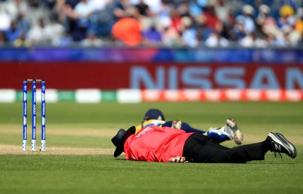 Cricketers lie on the ground during the World Cup match in Chester-le-Street. Picture: Owen Humphreys/PA