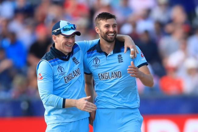 England's Mark Wood (right) celebrates taking the wicket of New Zealand's Mitchell Santner with team mates England's Eoin Morgan during the ICC Cricket World Cup group stage match at Riverside Durham, Chester-le-Street..