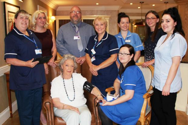 Staff from County Durham & Darlington NHS Foundation Trust and Manor House Care Home, with resident Barbara Moore