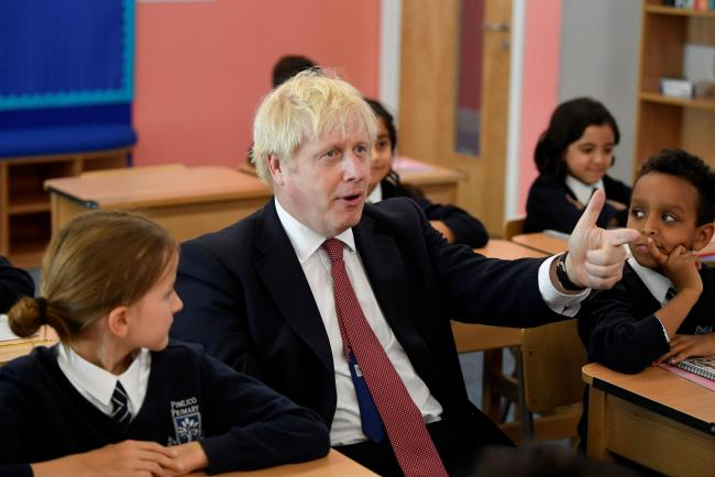 Prime Minister Boris Johnson chats with school children. Picture: Toby Melville/PA Wire