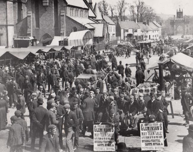 Bishop Auckland market 120 years ago - the sandwich-board boys' adverts at the front of the picture suggest it might have been a special May Day fair