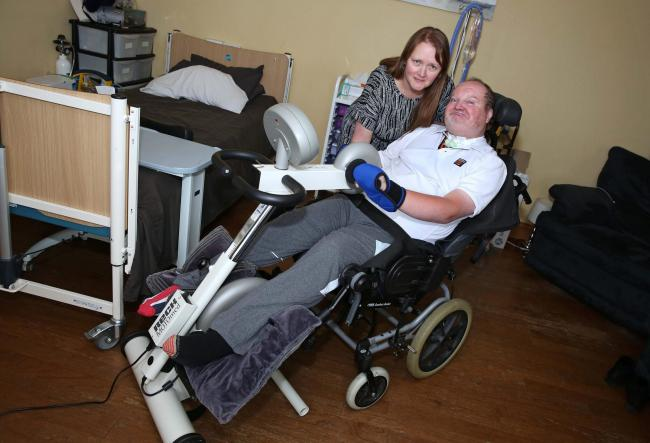 Steve Walsh, who has locked in syndrome, trying out the new exercise bike watched by his wife Michaela  Picture: RICHARD DOUGHTY PHOTO-GRAPHY
