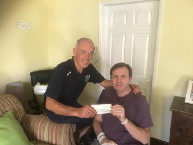 Steve Coulthard presents a cheque from a previous fundraiser to Richard Tremewan