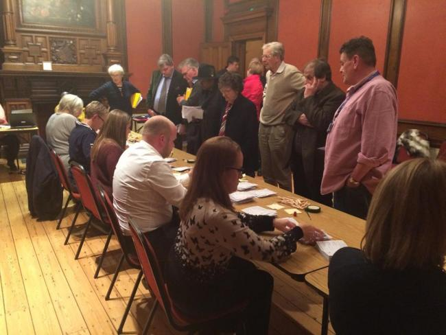 Council officers count the by-elections votes as candidates and their supporters look on