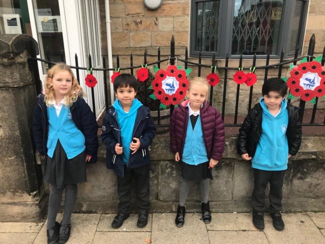 Year two children at Cestria Primary School with the poppies they made, and which have been affixed to the railings outside Durham Aged Mineworkers' Homes Association' s office in Chester-le-Street. The children have been learning about the sa