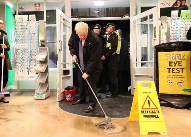 Prime Minister Boris Johnson helps with the clean up at an opticians as he visits Matlock on November 8