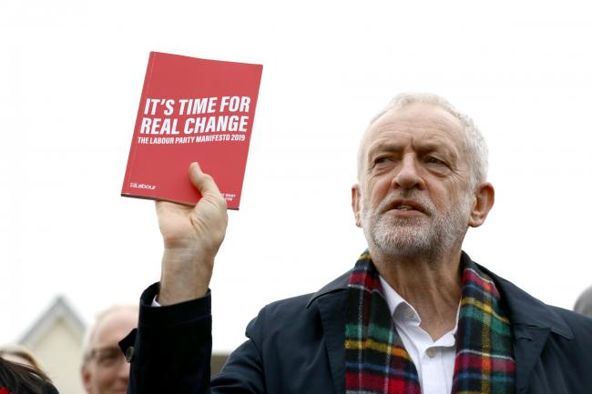 Labour Party leader Jeremy Corbyn, holds up his party's manifesto as he speaks to supporters during a visit to Thurrock in Essex whilst on the General Election campaign trail. Picture: Aaron Chown/PA Wire