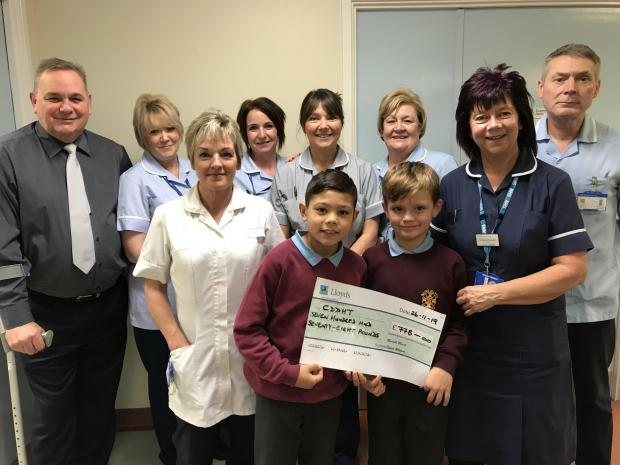 The Northern Echo: Steve Watson hands over the cheque to Sister Andrea Crampton and the orthopaedics team at the University Hospital of North Durham with the help of his son Bobby, left, and his friend Kirk