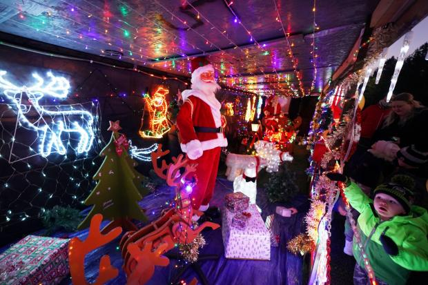 The Northern Echo: Members of the public view the Christmas lights belonging to Stan Yanetta, 58, in South Tyneside, where he has spent the last 3 weeks transforming his house with Christmas lights and decorations for children to enjoy. Picture: Owen Humphreys / PA Wire