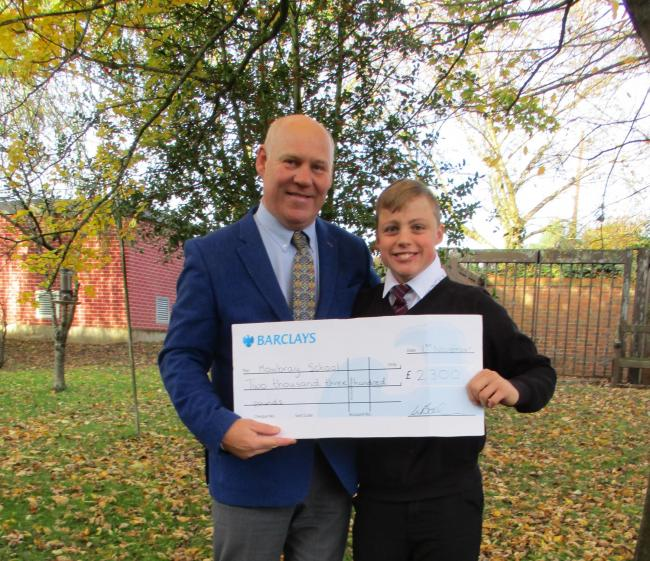 Jack hands over the cheque for £2,300 to Jonathan Tearle, head teacher of Mowbray school