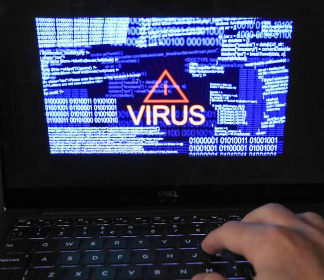 A stock image of a laptop screen showing a computer virus warning. Photo: Peter Byrne/PA Wire.