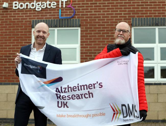 (L-R) Garry Brown and Mitchell Smith with the flag he will unfurl at Everest Base Camp when he attempts the gruelling trek later this month. He is doing the expedition in aid of Alzheimer's UK