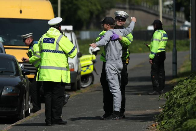 A man being searched at the roadside as police stop vehicles on the A23 road between London and Brighton near Patcham after the introduction of measures to bring the country out of lockdown. PA Photo. Picture date: Saturday May 16, 2020. See PA story HEAL