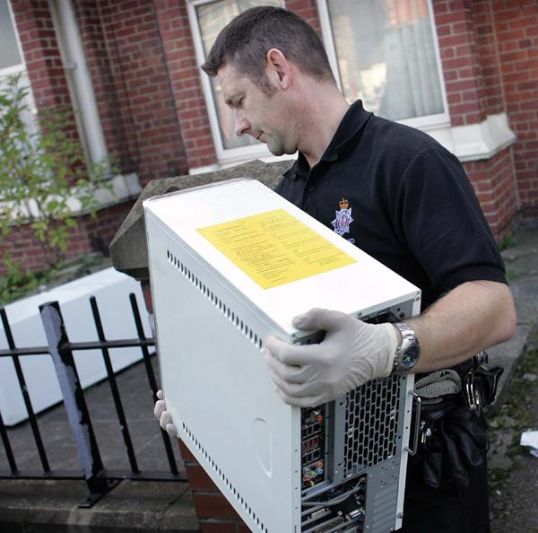 A police officer removes computer equipment from a flat in Grange Road, Middlesbrough, where a pirate file sharing operation, known as OiNK, was allegedly discovered