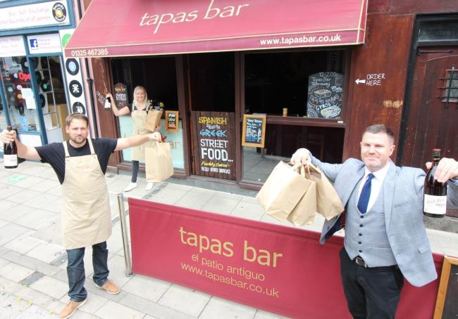 From left, George Turnbull and tapas bar manager Beccy Poad hand the takeaway orders to Ben Quaintrell
