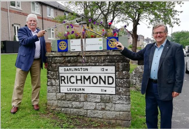 outgoing President Chris Kirby giving a socially distanced delivery of the Richmond Rotary chain of office to incoming President Warnock Kerr