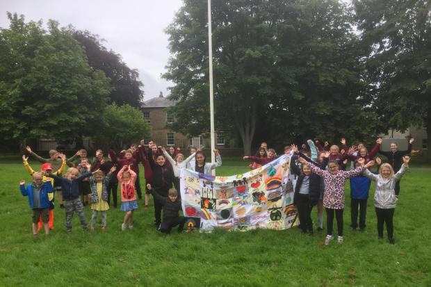 Pupils gather on Hurwort village green to see their flag raised. Picture: Peter Barron