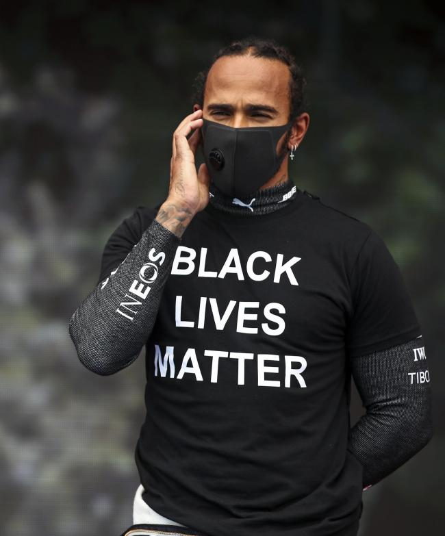 Mercedes driver Lewis Hamilton of Britain stands with a BLM shirt prior the the Hungarian Formula One Grand Prix race at the Hungaroring racetrack in Mogyorod, Hungary, Sunday, July 19, 2020. (Mark Thompson/Pool via AP).