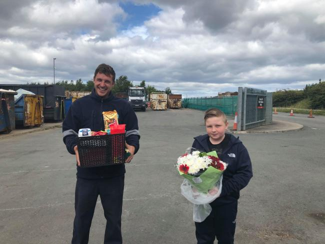 Refuse worker David Jeffries accepts thank you gifts from Izak Sidle