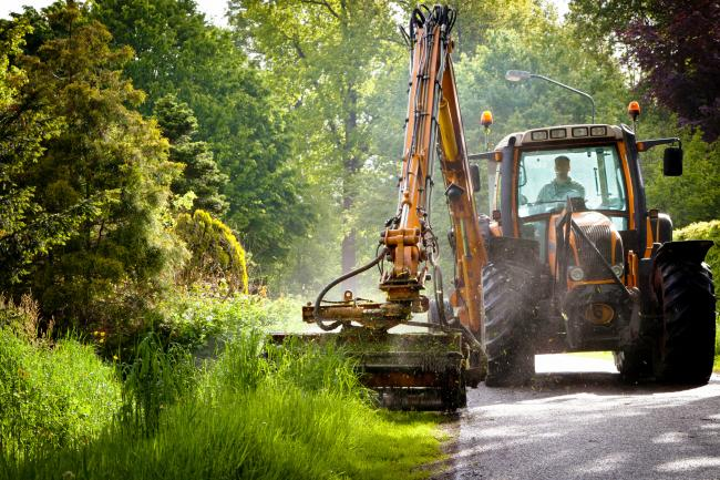 mowing grass verge with tractor .mowing grass shoulder along road with tractor mower in public space.