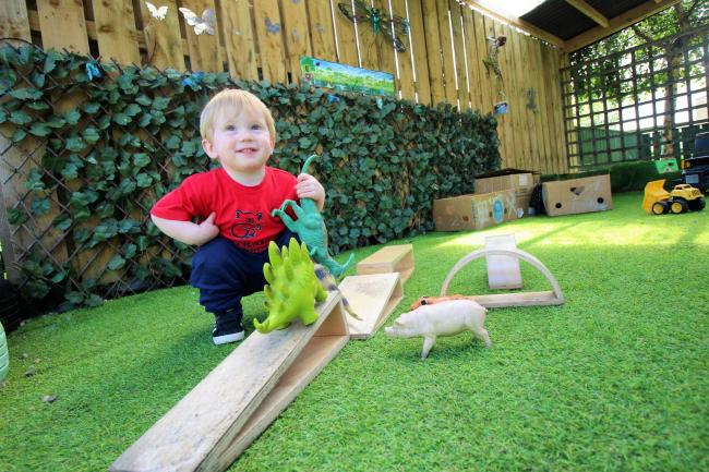 Theodore Pepe, one, enjoys the new artificial grass play area