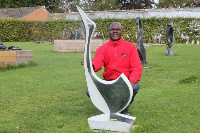 Dudzai Mushawepwere  with one of his sculptures at Newby Hall. Picture: Peter Barron