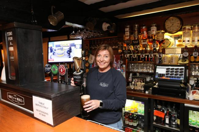 Joanne Shilliday pulling a pint in her pub The Hole In The Wall Bar, Armagh, Northern Ireland. Pubs and restaurants are to close for four weeks, with the exception of takeaways and deliveries, as new coronavirus restrictions were announced.
