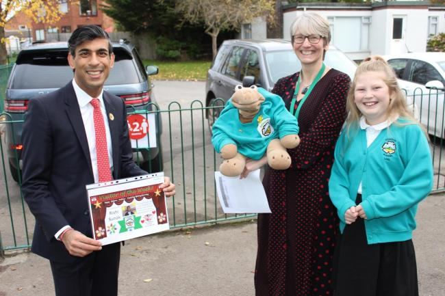 Rishi Sunak is greeted at Roseberry Academy by Headteacher Helen Channing, school mascot Stan and pupil Lois Vernon