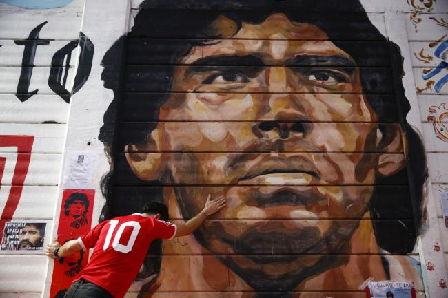 A boy touches a mural of Diego Maradona outside the stadium of Argentinos Juniors, where he started as a professional