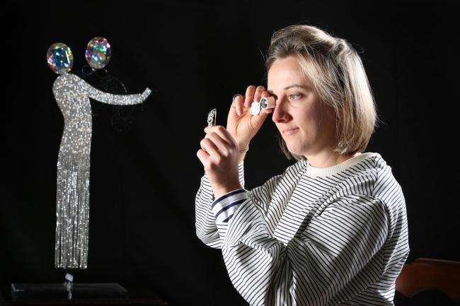 Junior valuer, Camilla Rawlinson, is pictured examining an Art Deco diamond bracelet with a Butler and Wilson figure of a dancing couple in the background