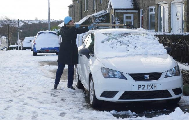 A woman clears snow from her car in Consett, County Durham. Picture: NORTH NEWS