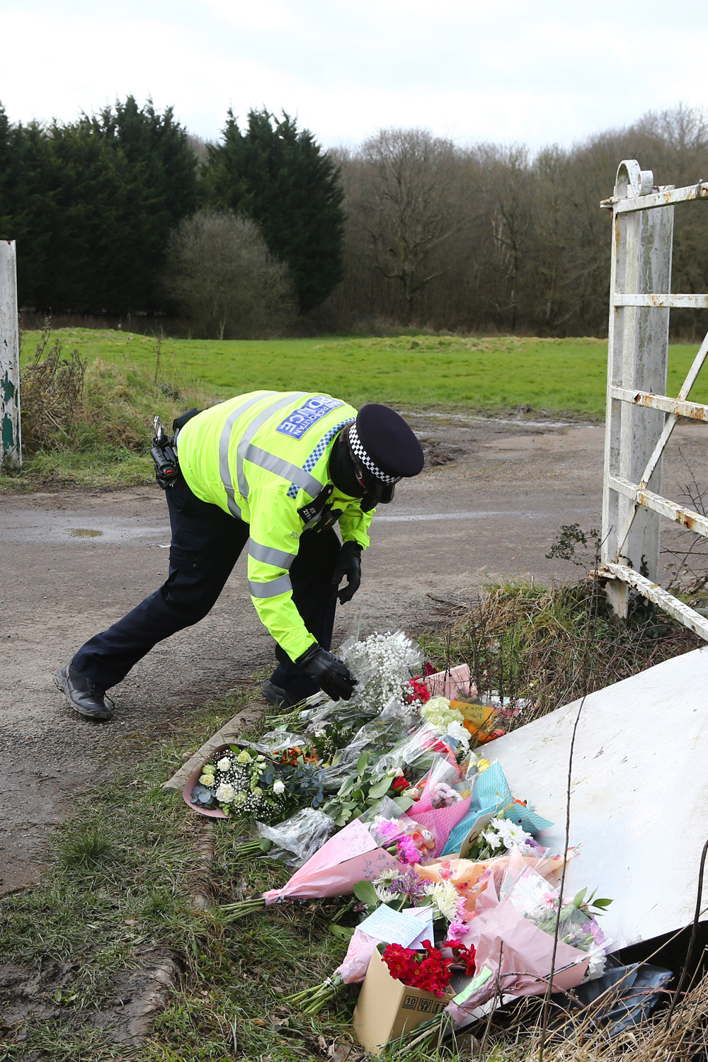 A police officer places flowers left by members of the public from the cordon to the site as Metropolitan Police continue their search near Great Chart, Kent after a body found hidden in woodland in Kent was identified as that of 33-year-old Sarah