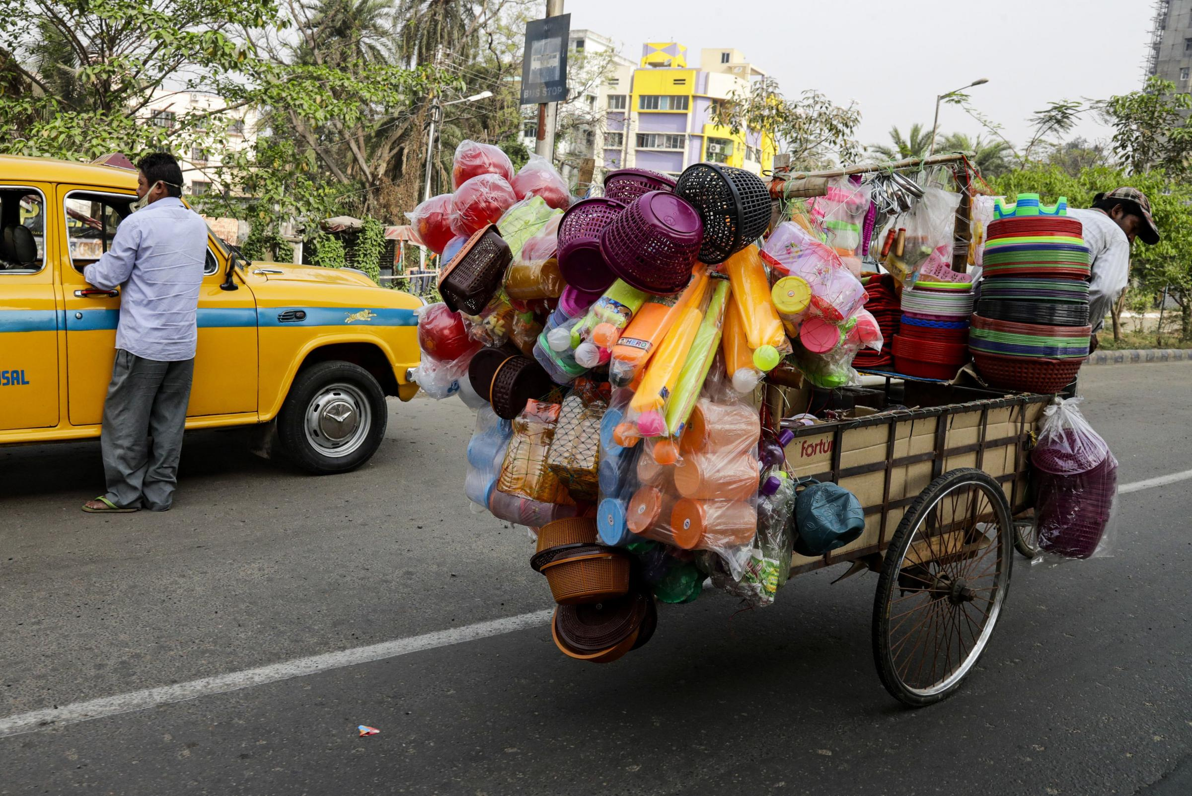 A man rides his cart filled with plastic utensils and toys, as a cab driver looks for passengers in Kolkata, India Picture: BIKAS DAS/AP
