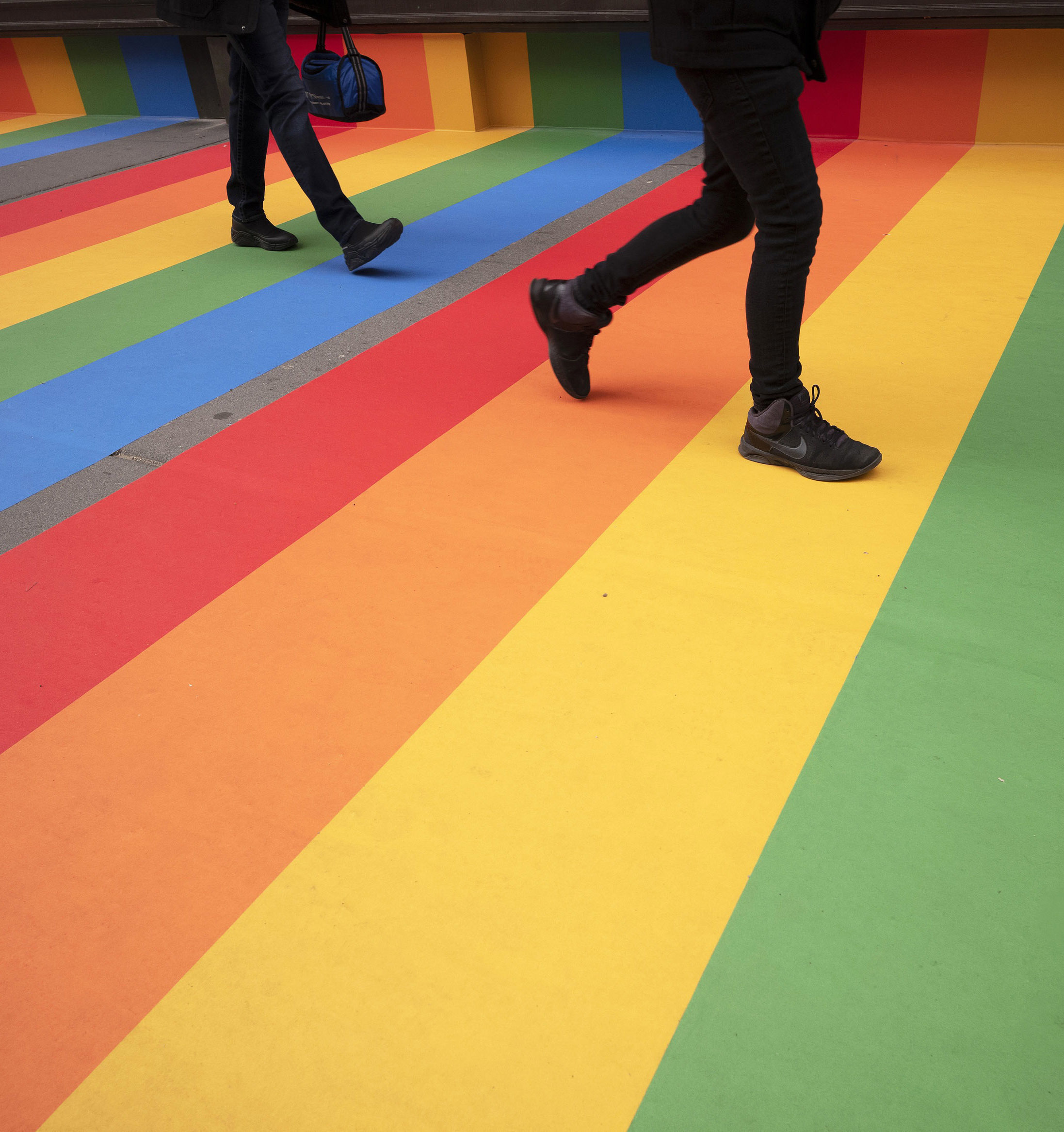 People walk along a Manhattan sidewalk that has been painted with brightly coloured stripes Picture: MARK LENNIHAN/AP