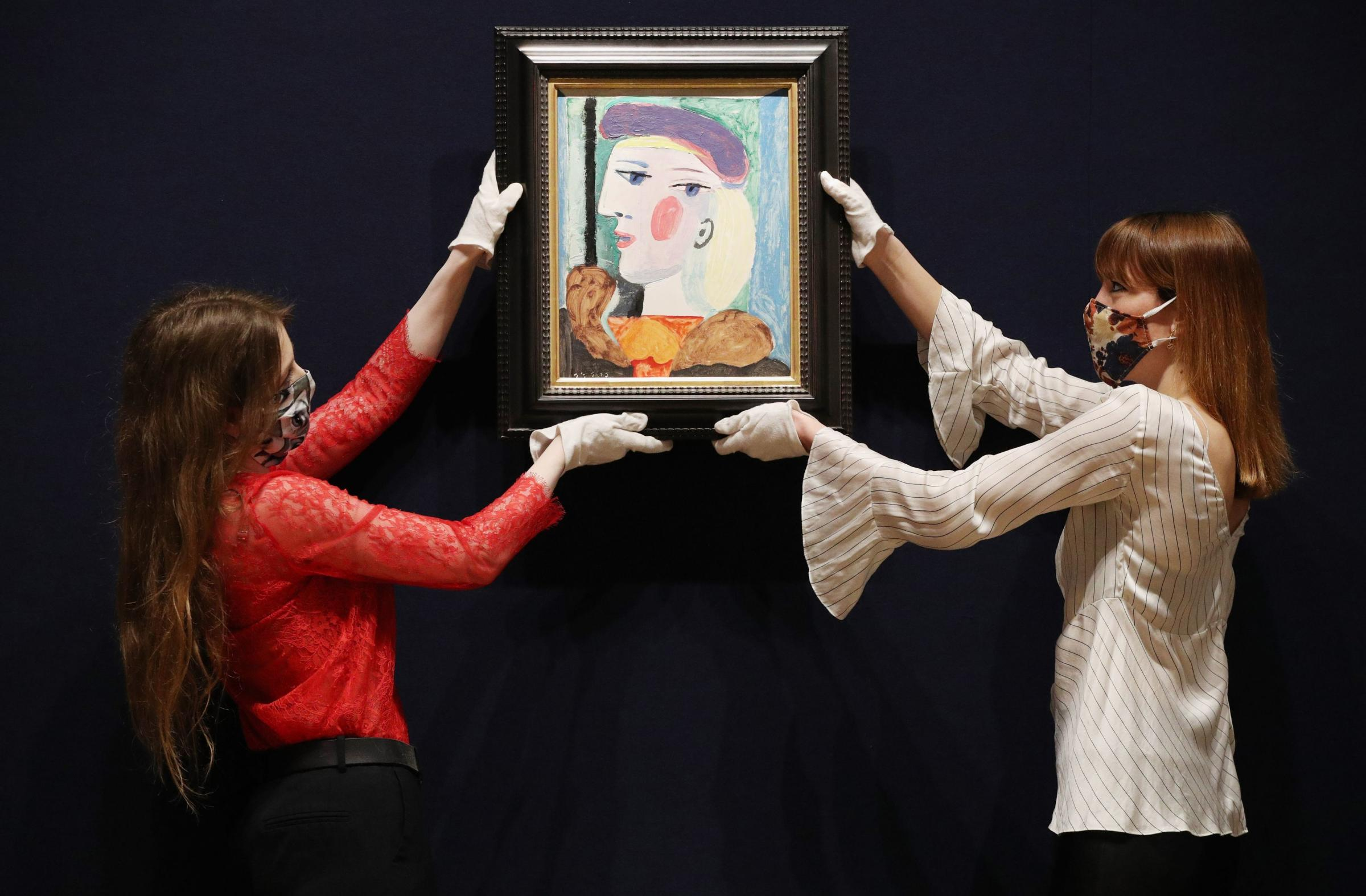 Picassos Femme au Beret Mauve is handled by employees at Bonhams in London before it is offered for sale and is estimated to fetch $10 million to $15 million when it is auctioned at their Impressionist and Modern Art sale in New York on Thursday, May 1