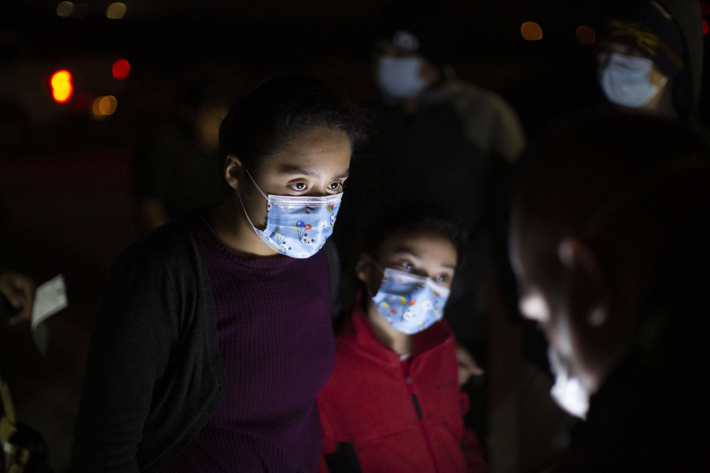 Fatima Nayeli, 13, left, and her sister, Cynthia Stacy, eight, answer questions from a US Border Patrol agent at an intake site after they were smuggled on an inflatable raft across the Rio Grande river in Roma, Texas. The sisters travelled from El