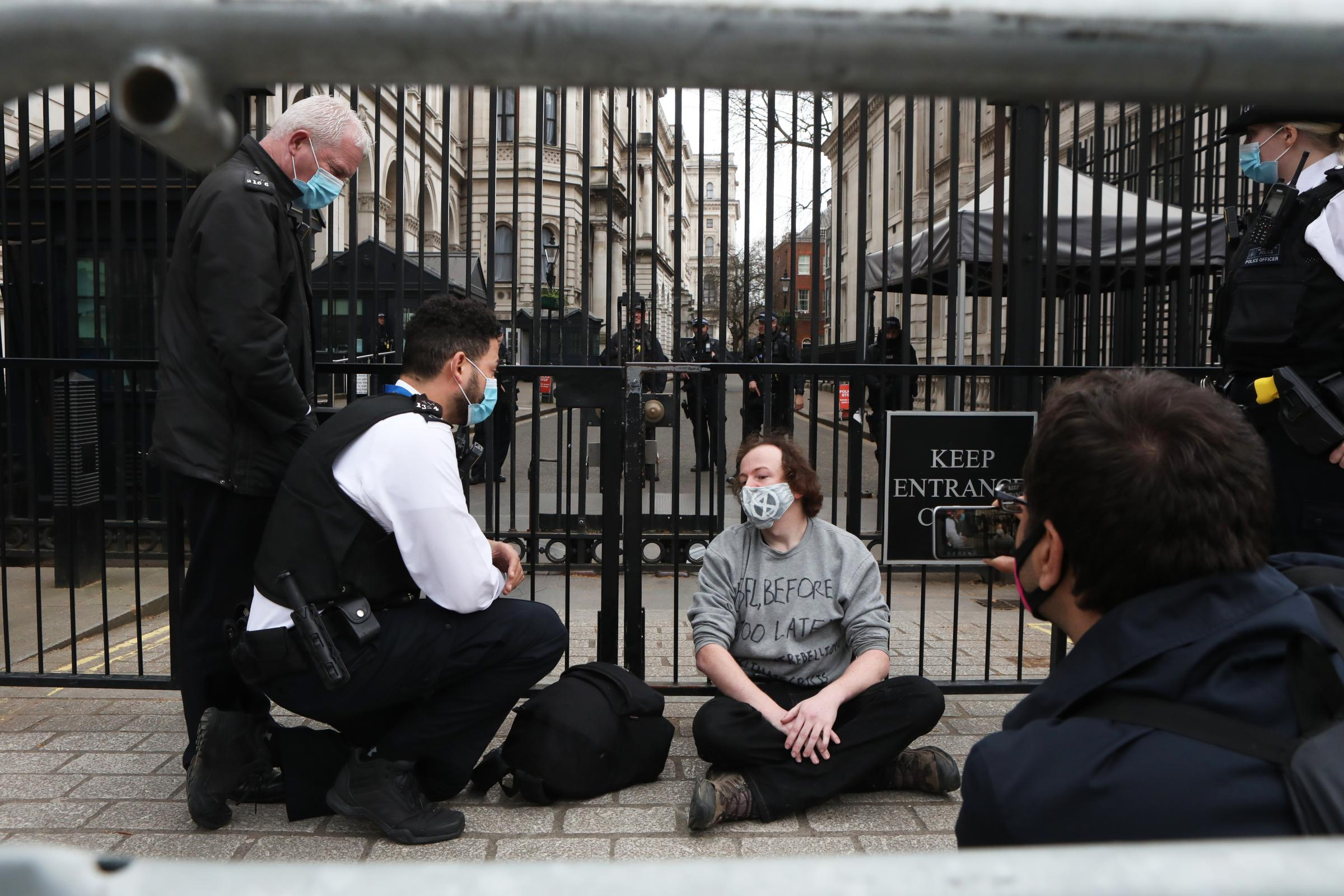 Police officers speak to a climate protester outside Downing Street in Westminster, London. Picture date: Wednesday March 24, 2021.