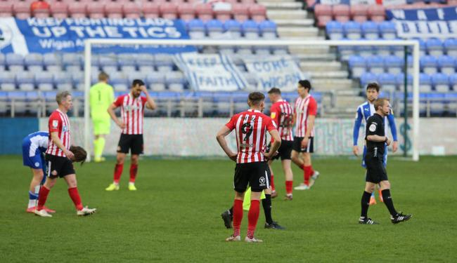 Sunderland's players show their disappointment in the wake of their 2-1 defeat to Wigan Athletic at the DW Stadium, a loss that leaves them five points adrift of the top two