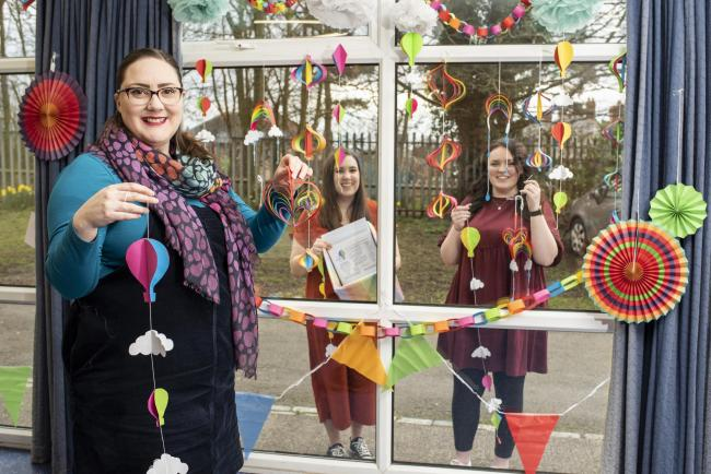 Rebecca with team members Erin and Kirsty and one of the decorated windows