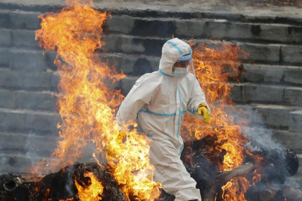 A Nepalese man in a protective suit walks between two pyres as he cremates the bodies of Covid-19 victims near Pashupatinath temple in Kathmandu, Nepal   Picture: NIRANJAN SHRESTHA / AP