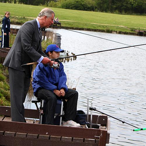 The Prince of Wales tries his hand at fishing with 13-year-old Paige Wardell during his visit to Hemlington Lake in Middlesbrough. Picture by Tom Banks.