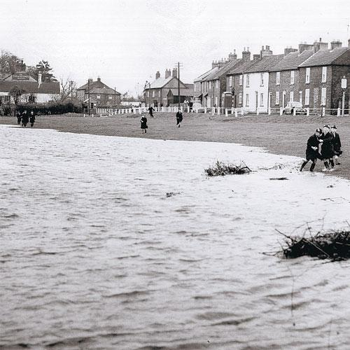 The Northern Echo: RISING DAMP: Schoolboys watch the river rise at Neasham on November 3, 1960. The Fox and Hounds is in the background. This picture appears in the fantastic new Echo Memories book, The Road to Rockliffe