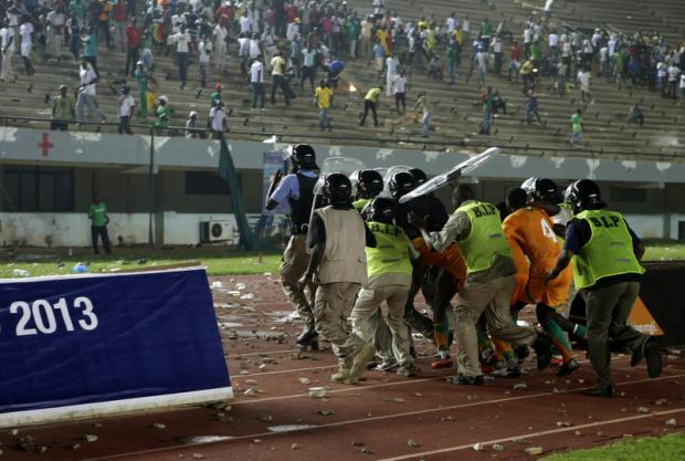 RIOTS: Ivory Coast players are ushered off the pitch as Senegalese fans riot after the Ivorians edged closer to victory in Dakar on Saturday