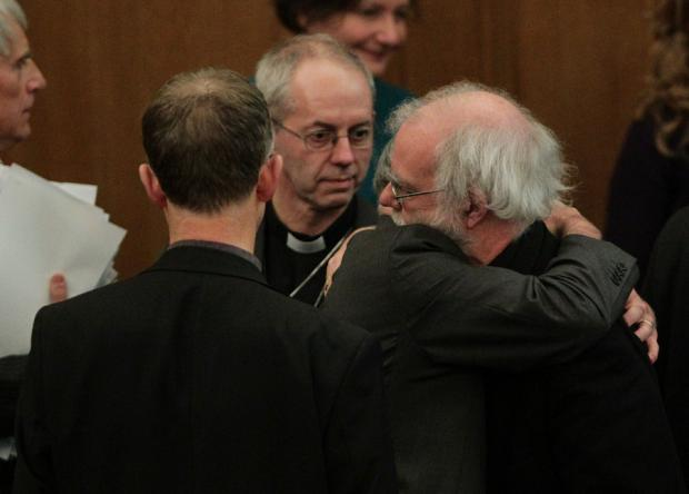 UNHAPPY RESULT: The Right Reverend Justin Welby, Bishop of Durham and incoming Archbishop of Cantebury, background, looks on as Dr Rowan Williams, the outgoing Archbishop of Canterbury is given a hug after church vote rejects women as bishops