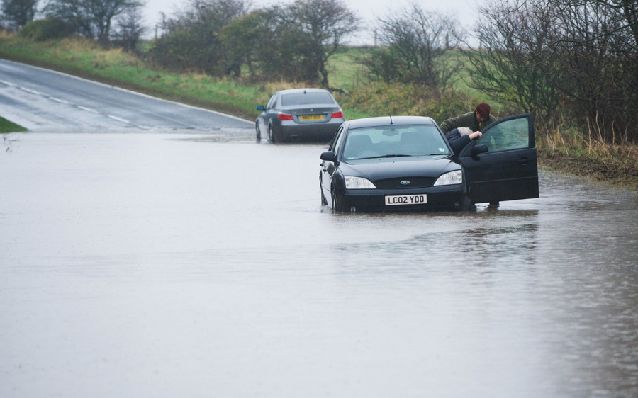 WATER TORTURE: A daughter helps her father from the car after becoming stranded in floodwater near to Staithes, North Yorkshire