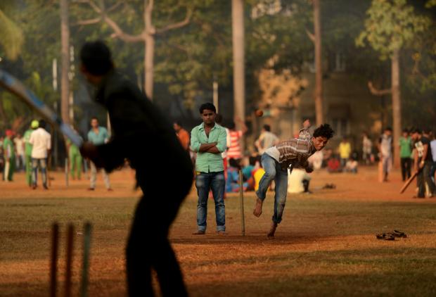 FULL PACE: A teenager bowls in bare feet at dawn on the Oval Maidan in Mumbai, India. Measuring 22 acres, the Oval Maidan is a Grade One recreational ground situated in South Mumbai