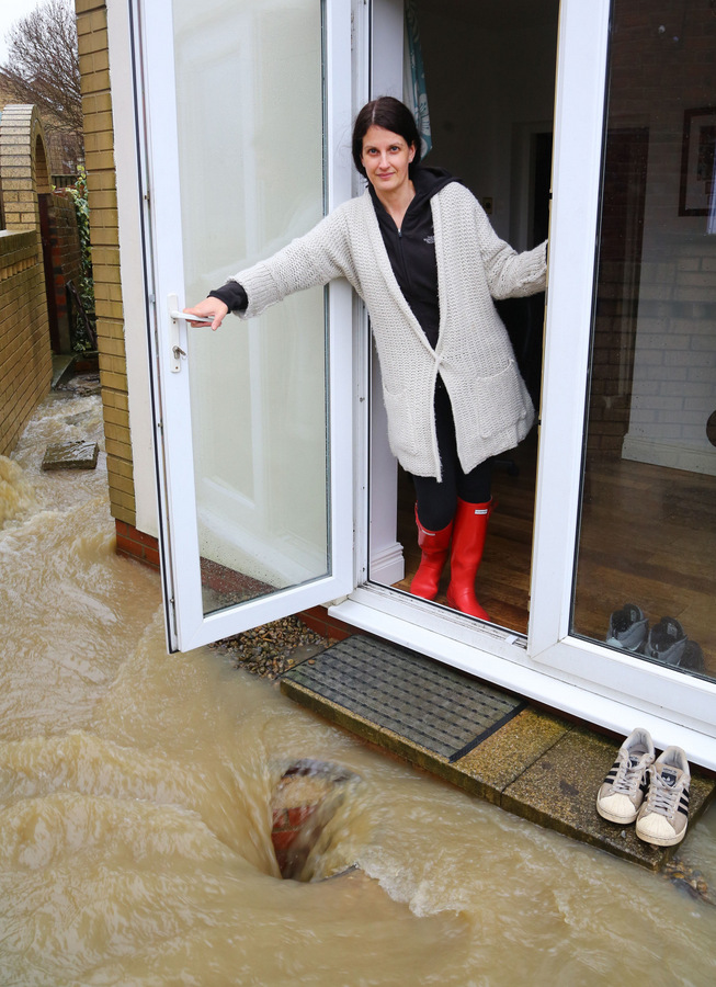 WATERFALL: Gaynor McCourt, of Wear View, Hunwick, at her front gate where water from an underground stream or culvert is gushing up from her back yard