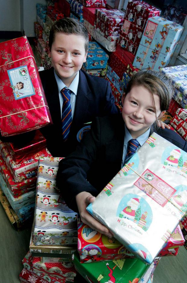 FESTIVE GOODIES: St Leonard's pupils Sara Mitchell, 11, and Luke Neil, 11, with some gifts their schoolmates have collected for needy youngsters around the world