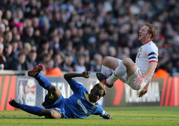 PAINFUL: AFC Wimbledon's Toby Ajala slides into MK Dons' Dean Lewington during their FA Cup second round tie yesterday. MK Dons won 2-1 and in the third round draw were handed a trip to Sheffield Wednesday