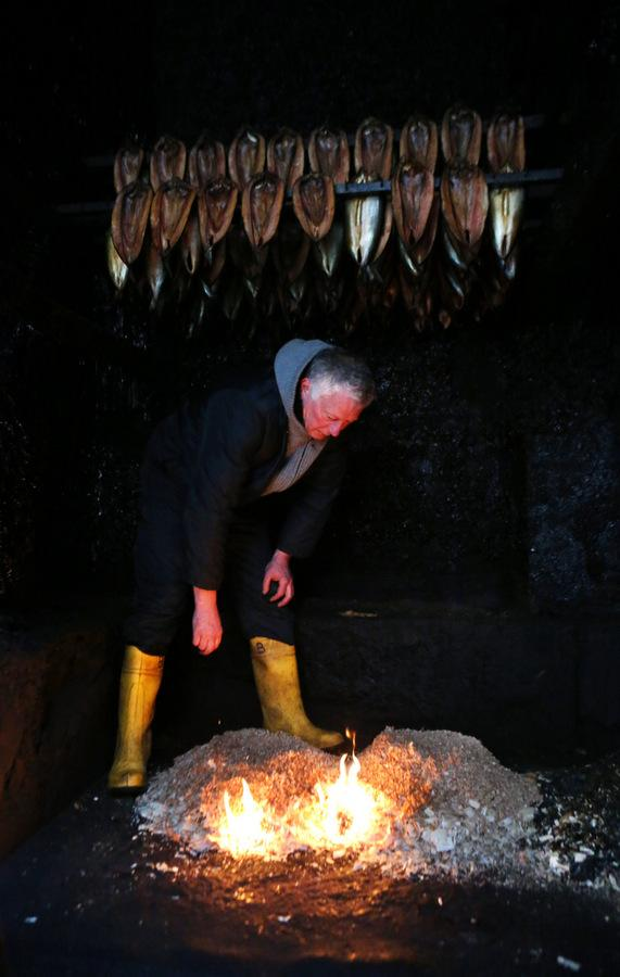 HOTTING UP: Barry Fortune lights a fire in the smokehouse